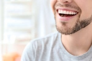 A man smiles while he wonders how to straighten teeth