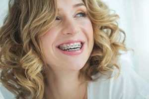 A woman with metal braces smiles