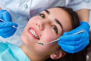 a girl with braces smiles undergoes Houston orthodontic treatment programs