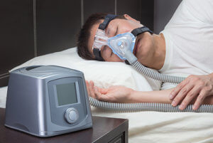a man uses a CPAP as one of his sleep apnea treatment options